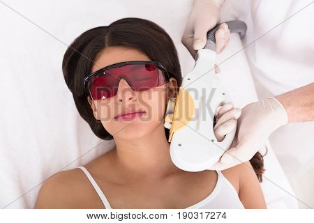 Young Woman Receiving Laser Epilation Treatment On Cheek In Beauty Spa