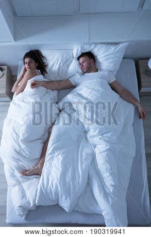 Elevated View Of Young Couple Sleeping On Bed At Home