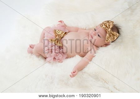Portrait of a four month old baby girl wearing frilly pink bloomers and a gold sequin bow headband. Shot in the studio on a sheepskin rug.