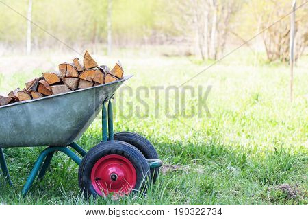Hand Truck With Neatly-stacked Firewood On The Green Grass In The Garden On Left Side Frame