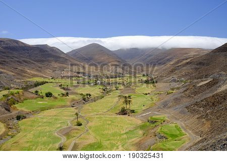 View on the green fields for golf between the mountains a beautiful whte cloud and blue sky on the Canary Island Fuerteventura Spain.