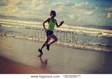 young fitness woman running on sunrise sandy beach