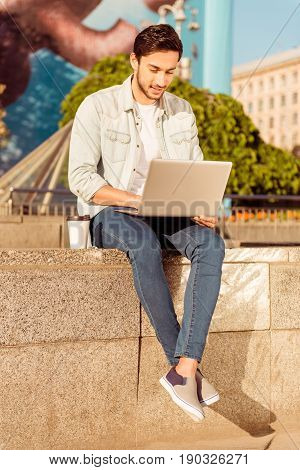 Young Handsome Bearded Brunete Is Browsing On His Laptop Outdoors On A Summer Day. Very Stylish And