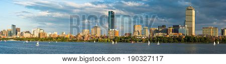 Boston Massachusettes Back Bay Distric with dark clouds behind and sailboats on the Charles River