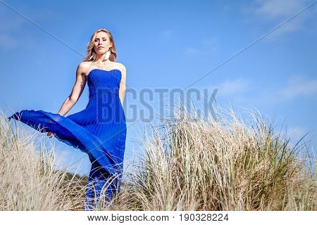 outdoor portrait of young beautiful blonde woman in blue gown posing on natural sky background