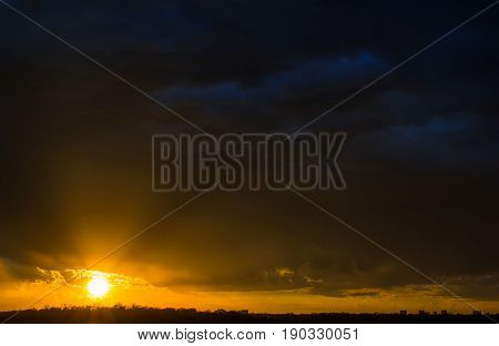 Stormy sunset with rolling clouds and light rays. Very Dark
