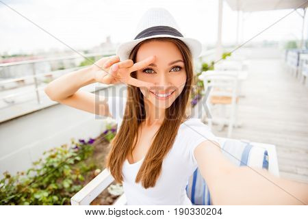 Cute Young Girl With Toothy Beaming Smile Is Making Selfie On A Camera Of Her Pda. She Is Wearing Ca
