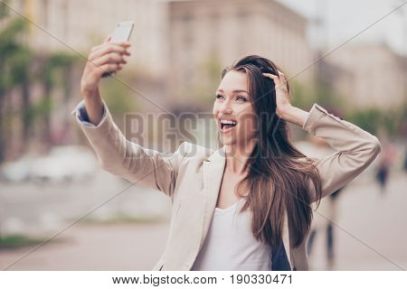 Selfie Mania! Excited Young Girl Is Making Selfie On A Camera. She Is Wearing Formal Wear, Fixing He