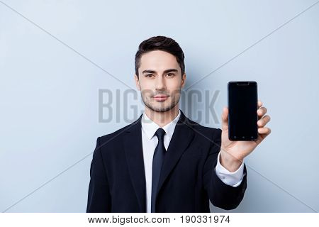 Handsome Young Guy Finance Broker With Stubble Is Holding Phone With Black Screen. He Is Wearing For