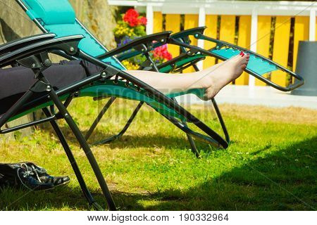 Female bare feet. Woman relaxing on sunbed or deck chair in her garden during sunny weather.