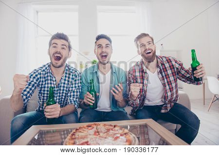 Goal! Cheerful Young Guys Are Watching Match On Couch At Home And Drink Beer, Eat Pizza On The Sofa