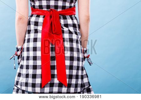 Retro pin up elegant and timeless clothes concept. Woman wearing retro checked black and white dress with big red bow studio shot on blue background