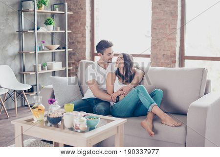 Cute Couple In Love In The Weekend Morning. They Are Hugging On The Sofa Indoors At Home, Wearing Ca