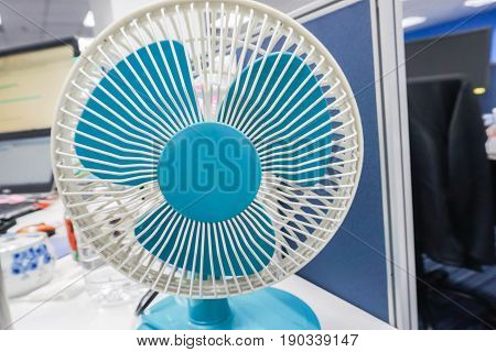 close up portable blue table fan in office
