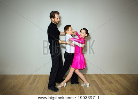 The young boy and girl with male coach or teacher posing at dance studio on gray. The ballroom dancing school and education concept