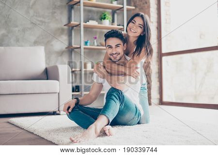 Love You! Cheerful Beautiful Couple Hugging At Home. They Are So Happy, Wearing Casual Clothes, Sitt
