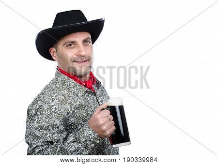 Portrait of cowboy holding glass tankard of porter beer on white background. Friendly man wears black hat red scarf and white gray patterned shirt with long sleeve