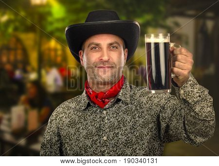 Forty years old cowboy toasting with tankard of porter beer on blurred outdoors night pub background. He wearing black hat red scarf and white gray patterned shirt