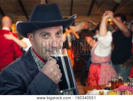 Forty years old man in black cowboy hat drinks glass of stout beer. Farmer wearing dark gray jacket stands on blurred background of dancers in western saloon. Medium close-up horizontal portrait.