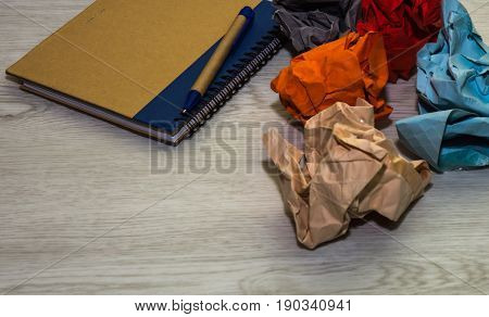 Colorful paper and notebook on white wooden background.