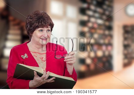 Funny older female professor reads big book and laughs  at the same time. Woman wearing red jacket holds glasses with left hand on blurred library background.