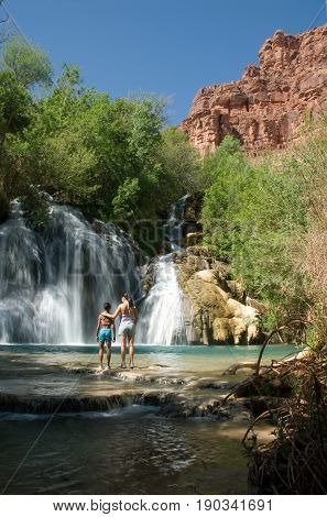 Mother and Daughter standing in front of Navajo Falls on Havasu Creek Arizona.