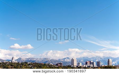 Skyline of Salt Lake City Utah. Scene includes the Utah State Capitol Building the downtown skyscrapers and the world famous Mormon Temple with the Wasatch Mountain Range in the background. Lots of room for type in the image.