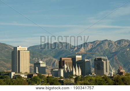 Skyline of Salt Lake City Utah with a storm approaching. The image shows the downtown buildings and skyline the historic Mormon temple and the Wasatch mountains in the background.