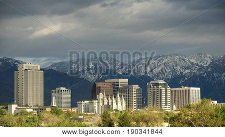 kyline of Salt Lake City Utah with a storm approaching. The image shows the downtown buildings and skyline the historic Mormon temple and the snow capped Wasatch mountains in the background.