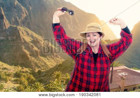 Tireless older woman in yellow straw hat backpacking. She wearing red plaid shirt poses on blurred mountains background are flooded by sunrise. Her right hand holds sunglasses. Older people traveling concept.