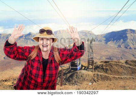 Energetic retired woman wearing red plaid shirt having fun on blurred mountain cable background. Older people traveling concept