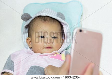 Close Up Cute new born baby looking mobile phone in hand.