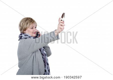 Self-assured 60 years old businesswoman catches taxi by left hand with glasses. Standing woman in gray cardigan talks by mobile phone at the same time. Horizontal profile mid shot on white background