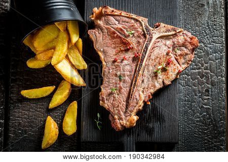 Homemade Tbone Steak With Chips On The Burnt Table