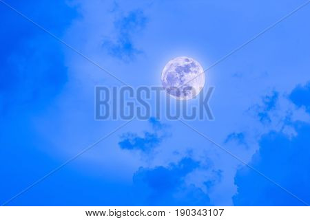 The Moon at it largest also called supermoon with blue sky and clouds.