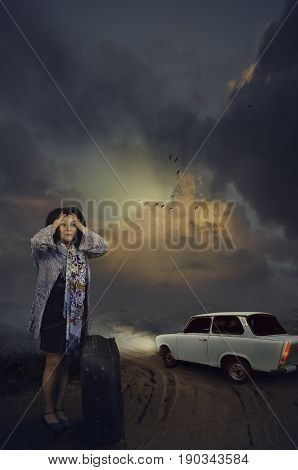 Woman panics on the desert road at night. White car drives away. Scared mature woman holds her head with hands. It seems she was landed from auto. Flock of birds flies in dramatic clouds in the dark sky. Horror concept