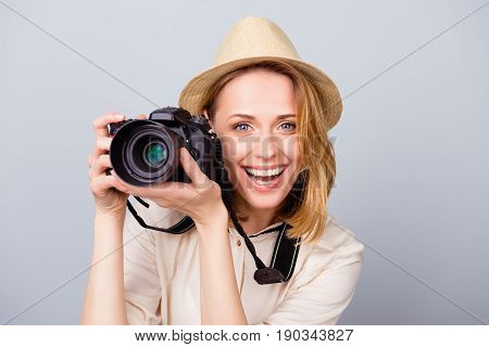Young Cheerful Blond Female Photographer Is Smiling On The Light Blue Background. She Is Excited And