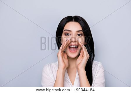 Hey! Cheerful Young Lady In White Casual Shirt Is Shouting And Holding Hands Near To Open Mouth On L