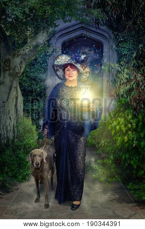 Aged fairy and weimaraner dog came out of dark archway surrounded by lush foliage. Woman holds the leash right hand, and lamp by left. She wears a black guipure clothes and big tapestry hat with feathers. Vertical shot