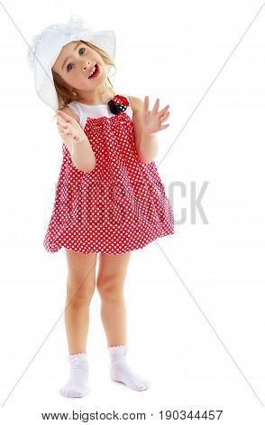 Full growth.Joyful little girl in a very short polka dot dress and white Panama city beach , claps.Isolated on a white background.