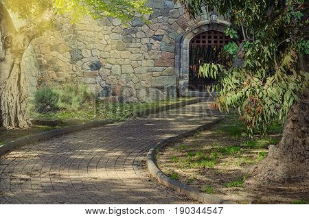 Footpath in lush park leading to rear arched entryway in stone medieval wall. Sunset floods the tree and part of the wall in left side. There are light spots on the pathway