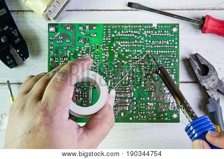 Serviceman Soldering Circuit Board With Soldering Iron In The Service Workshop