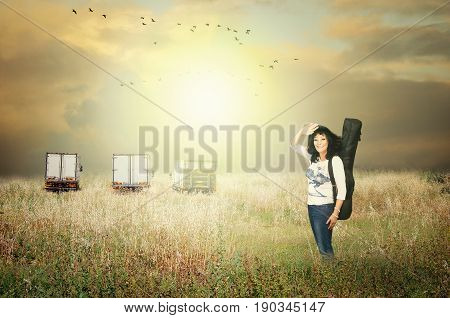 Mature adult woman singer posing with guitar in black case on three white cargo trucks parked in high rural yellow grass field background. A flock of birds flies in stormy sky over the land