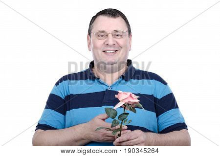 Optimistic older man holding a rose by hand and looking at the camera on white background. Middle-aged guy wearing glasses and striped polo shirt. Horizontal medium close-up shot