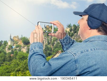 Traveling fat man with chubby face takes medieval house pictures on mountain top with mobile phone. Fifty years old man wears denim shirt and cap with ear flaps. Older people tourism concept. Mid side shot