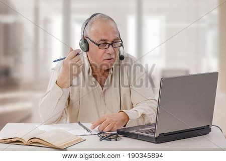 Older male freelancer in headset sits in front of laptop computer. Retired man in light beige shirt setts up his own online tutoring business. Horizontal indoors shot on blurry home office background