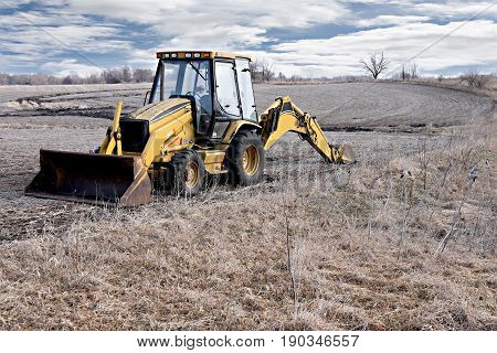 Yellow tractor in barren field against blue cloudy skies