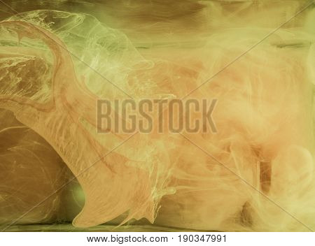 Abstract colored background. Yellow smoke, ink in water, the patterns of the universe. Abstract movement, frozen multicolor flow of paint. Horizontal photo with soft focus, blurred backdrop.