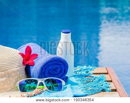 Red frangipani (plumeria) flowers sunglasses beach hat blue towel and sunscreen at the side of swimming pool. Vacation beach summer travel concept