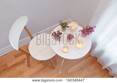 Cozy home interior with white chair and table decorated with candle lights and spring flowers.